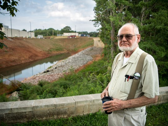 Brian Paddock, of the Sierra Club, poses for a portrait outside of a construction site that borders wetlands in Cookeville, Tenn., Tuesday, July 17, 2018. The construction is seen at left, and the remaining wooded wetlands are to the right.