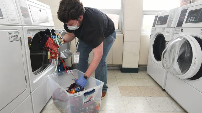 Joe Theiss transfers cloth face masks into a dryer, at left, from a washing machine as part of a project to clean about 5,000 masks for the Erie County Department of Health on May 6 in a dormitory at Mercyhurst University. Theiss, 21, is a volunteer with the Erie County Department of Health's Medical Reserve Corps.