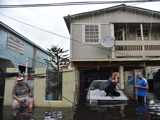 Inhabitants stand in flood water in front of a house