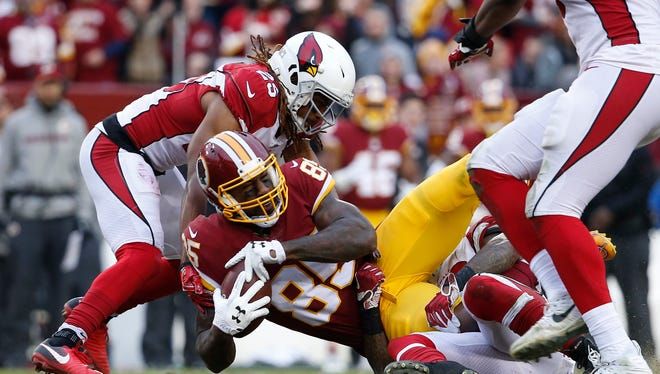 Dec 17, 2017: Washington Redskins tight end Vernon Davis (85) is tackled by Arizona Cardinals inside linebacker Deone Bucannon (20) and Cardinals defensive back Tramon Williams (25) during the second half at FedEx Field. The Redskins won 20-15.