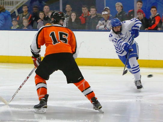 Catholic Central's Ethan Ervin (right) fires a shot