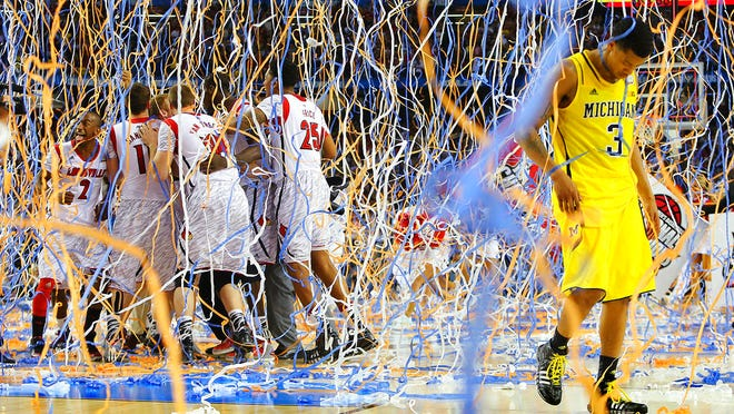 From  April 8, 2013, Michigan guard Trey Burke (3) walks off the court as confetti falls on Louisville players, including Russ Smith (2), Luke Hancock (11), Stephan Van Treese (44) and Zach Price (25), after the NCAA Final Four tournament college basketball championship game in Atlanta. Coronavirus stopped March Madness before it could begin, meaning there would be no men's national college basketball tournament and no championship game. The virus also silenced another long-standing tradition, but Max Goren refused to let that tradition die.