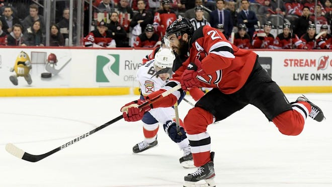 New Jersey Devils right wing Kyle Palmieri (21) scores on a shot as he is checked by Florida Panthers defenseman Riley Stillman (61) during the second period of an NHL hockey game Tuesday, Feb. 11, 2020, in Newark, N.J.