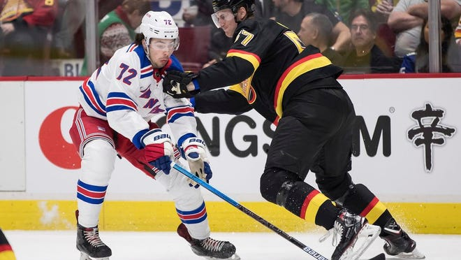 Vancouver Canucks' Tyler Myers, right, checks New York Rangers' Filip Chytil, of the Czech Republic, during the first period of an NHL hockey game Saturday, Jan. 4, 2020, in Vancouver, British Columbia.