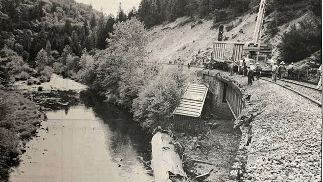 In this photo from the July 17, 1991 edition of the Dunsmuir News, Southern Pacific crews worked to clear tracks of seven cars and an engine that infamously  derailed days before, spilling thousands of gallons of a weed killer into the Sacramento River. The white tanker that leaked Vapam is shown lying upside down in the water underneath the trestle.