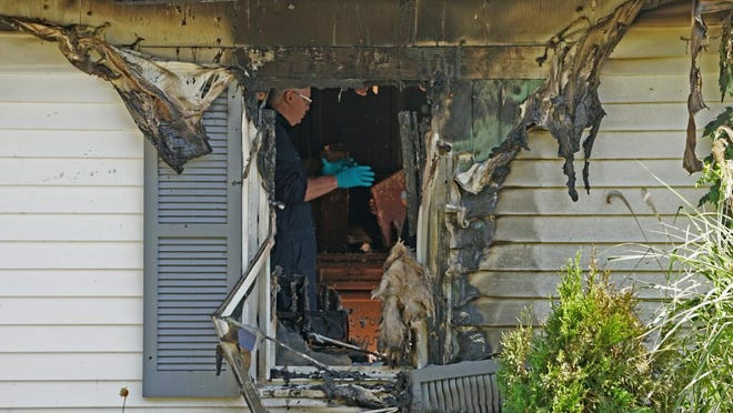 An investigator works inside the house on Namquid Drive, Warwick, where a person was found dead.