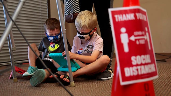 """Lincoln, left, and Ben Miller play video games as their mother Holly Miller casts her absentee ballot at the St. Louis Board of Election Commissioners on Monday, Aug. 3, 2020. """"I felt it would be really hard in a pandemic to take them tomorrow,"""" said Miller. The election board has been busy with a sharp rise in absentee voters."""