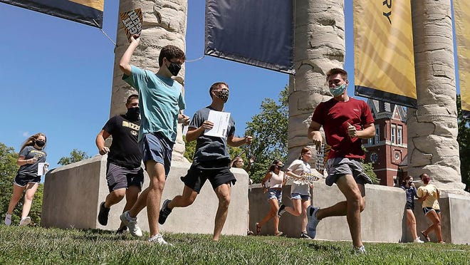 Incoming freshmen run through the University of Missouri columns on Aug. 19, 2020, for the Tiger Walk, in Columbia, Mo. As waves of schools and businesses around the country are cleared to reopen, college towns are moving toward renewed shutdowns because of too many parties and too many COVID-19 infections among students.