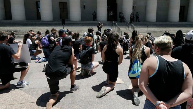 Demonstrators take a knee during a prayer at the Ohio Statehouse in Columbus on Sunday, June 7.