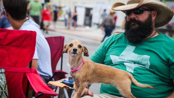 Dusty Daniel holds his dog, Lexi, on his lap while listening to music during the Simply Texas Blues Festival Saturday, May 19, 2018, in downtown San Angelo.
