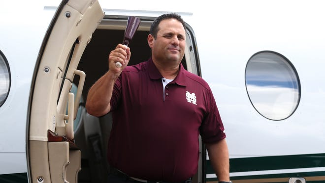New Mississippi State baseball coach Chris Lemonis steps off the plane in his Mississippi State shirt, ringing his cowbell.