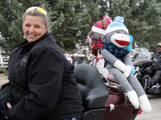 Michele Cope and waits with a pair of sock monkeys prior to the annual Toy Run.