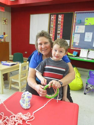 Jackie Chow works with a student to weave an infant hat on a loom. Students in the St. John Lutheran 4K class learned how to weave with volunteers and grant funding.