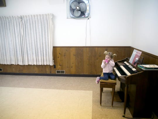 Lily Watson, 2, drinks from her cup as she sits on the organ inside of the Gilberton Community Club.