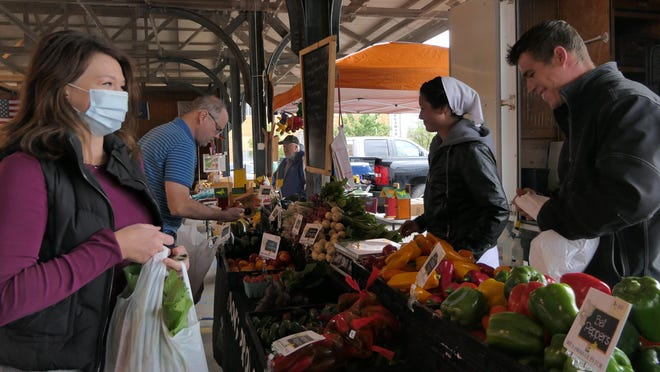 Ginny Clary, of Hutchinson, purchases spinach and turnips from Samuel Miller, of Don's Produce, at the Reno County Farmers Market on Oct. 3 in Hutchinson.