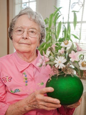 In this file photo, Velma Cox of Manitowoc poses for a portrait with the first French beaded flower bouquet she made at her Felician Village apartment.
