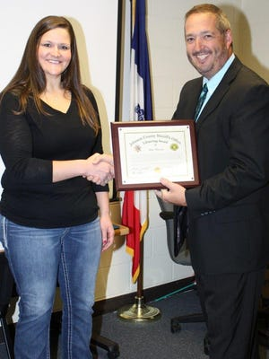 Sheriff Lonny Pulkrabek, right, presents Johnson County Jail control center operator, Kim Pearson, with the Sheriff's Office Lifesaving Award at a ceremony on Nov. 10 in honor of her efforts to save the life of an inmate in July.