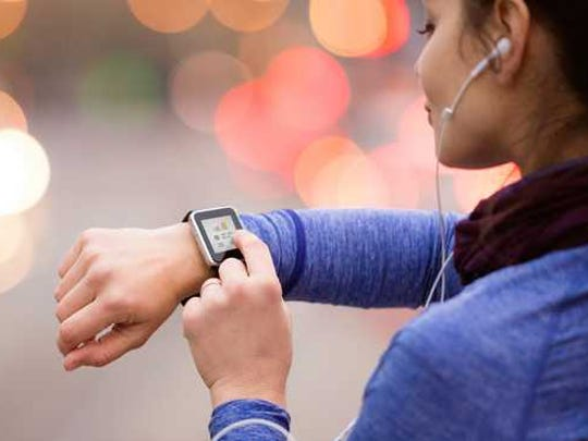 A woman wearing headphones and checking her smartwatch