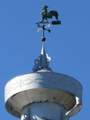 A copper rooster weather vane sits atop a barn on a