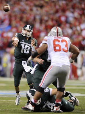 Michigan State's Connor Cook throws the ball against Ohio State during the first half of the Big Ten Championship game, Saturday, December 7, 2013, at Lucas Oil Stadium.