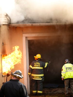 Flames shoot through a west window of an Elmira Heights garage as fire personnel enter the building. The wind picked up moments before the burst of flames.