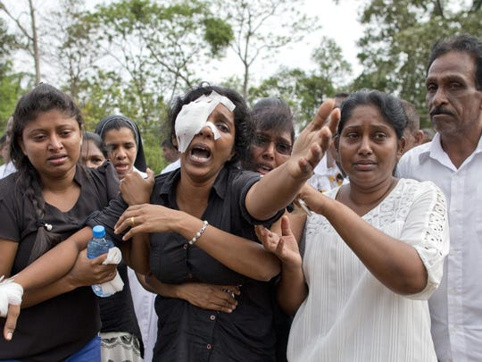 Anusha Kumari, second from left, weeps during a mass burial for her husband, two children and three siblings, all victims of Easter Sunday's bomb attacks, in Negombo, Sri Lanka, Wednesday, April 24, 2019.