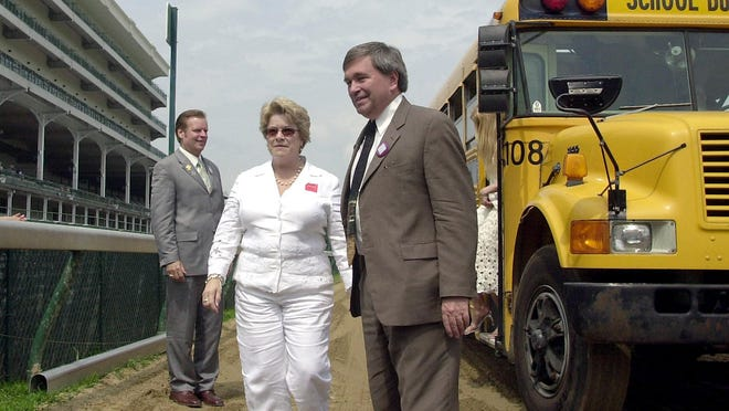 In this Saturday, June 14, 2003 file photo, Jack Knowlton (right) and his wife, Dorothy, along with Dave Mahan (left) part of the ownership of Kentucky Derby champion Funny Cide, returned to Churchill Downs in Louisville, Kentucky, to accept the engraved winner's trophy. The yellow school buses are on reserve as Knowlton and his merry band from Sackatoga Stable are back at the Kentucky Derby for the first time in 17 years, this time with a horse everyone knows.