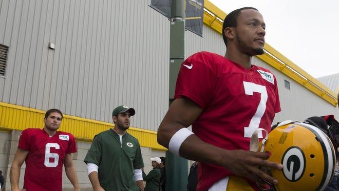 Packers quarterbacks Brett Hundley (right) and Joe Callahan (left) take the field during training camp.