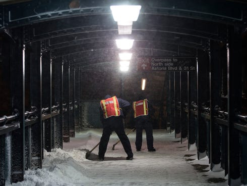 Workers clear snow from a pedestrian passageway at the Astoria Blvd. subway station on Friday in the Queens borough of New York.