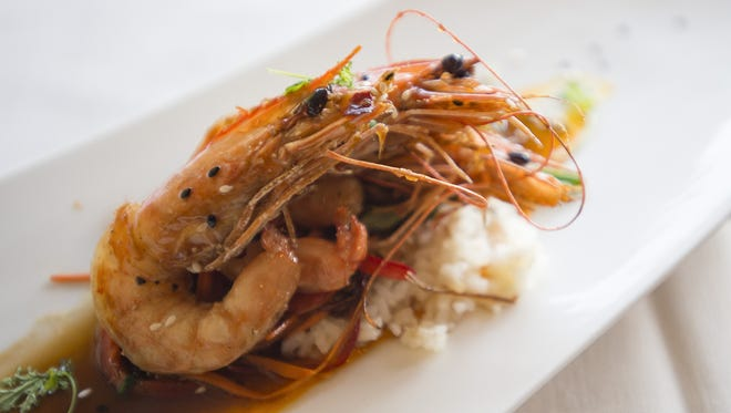 Glazed New Caledonian prawns are served over a bed of  Carolina Gold Rice, carrot-ginger puree and vegetables at Chimney Park Restaurant and Bar in Windsor.