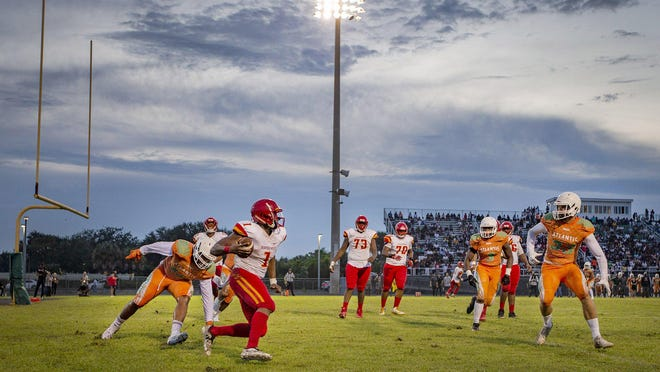Deerfield Beach quarterback Derohn King (1) is chased by Atlantic defensive end Zyin Thomas (15), linebacker Miciah Joseph (3) and defensive end Bruce Adlar (33) before being dropped in the end zone for a safety in the second quarter in Delray Beach on August 15, 2019.