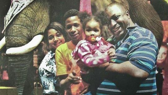 In this undated family photo provided by the National Action Network, Saturday, July 19, 2014, Eric Garner, right, poses with his children during during a family outing.