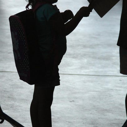 A girl is silhouetted after choosing her backpack during the 2013 Fill a Backpack Fill a Need event.