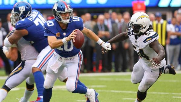 New York Giants quarterback Eli Manning (10) runs with the ball while under pressure from Los Angeles Chargers outside linebacker Melvin Ingram (54) during an NFL football game Sunday, Oct. 8, 2017, in East Rutherford, NJ. Eli Manning still has as many wins this season as his two brothers, Peyton and Cooper.