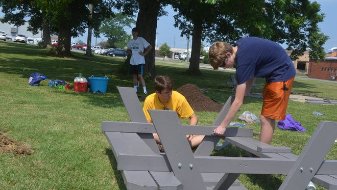 Connor Covington, in the yellow shirt, spent his Eagle Scout project Friday, June 15 creating a picnic table area for the Hendersonville Police Department.