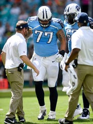 Titans offensive tackle Taylor Lewan (77) walks off