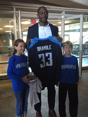 Titans marketing coordinator Toks Sokoya presented Baylor Bramble's siblings Macy and Brady a Titans jersey and a signed mini helmet on Tuesday.