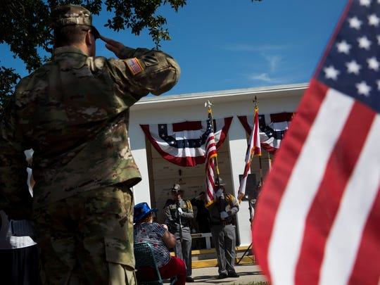 Retired Army Sgt. 1st Class Vince Phillips, an officer with the Naples High JROTC and member of the Veterans Council, salutes during the national anthem as veterans and family members of those who lost loved ones while serving came together to honor those fallen during a Memorial Day service at the Naples Memorial Gardens at Hodges Funeral Home on Monday, May 29, 2017.