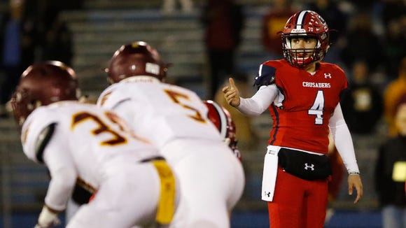 Stepinac quarterback Michael Nicosia (4) signals his