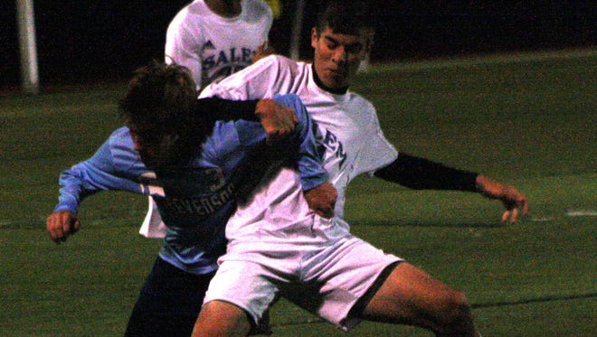 Livonia Stevenson's  Sam Landefeld (left) battles for possession of the ball with Salem's Hunter Gibbons.