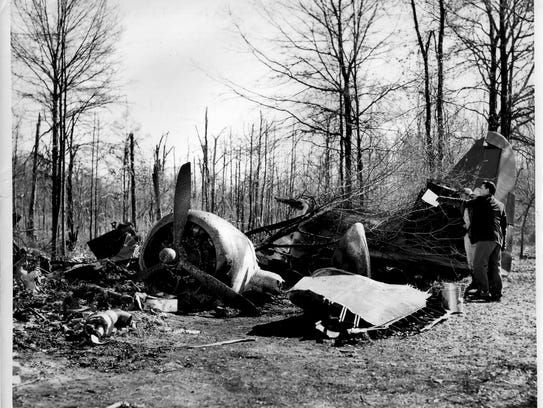 Officials survey the wreckage of a Jan. 10, 1954, airplane