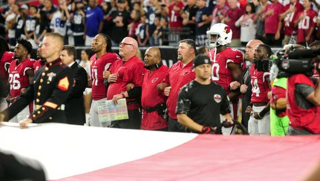 Sep 25, 2017: Arizona Cardinals wide receiver Larry Fitzgerald (11) , head coach Bruce Arians and teammates stand in front of a giant flag during the national anthem prior to the game against the Dallas Cowboys at University of Phoenix Stadium.