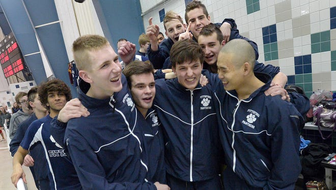 Led by their four captains, Pittsford swimmers walk to the podium to accept their team trophy following the Section V Class A Boys Swimming Championship Finals held at Webster Aquatic Center in February.