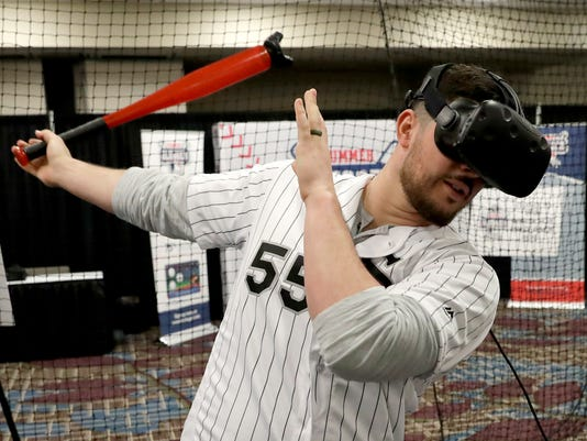 Chicago White Sox's Carlos Rodon tries out a virtual reality batting cage during the baseball team's convention Friday, Jan. 26, 2018, in Chicago. (AP Photo/Charles Rex Arbogast)