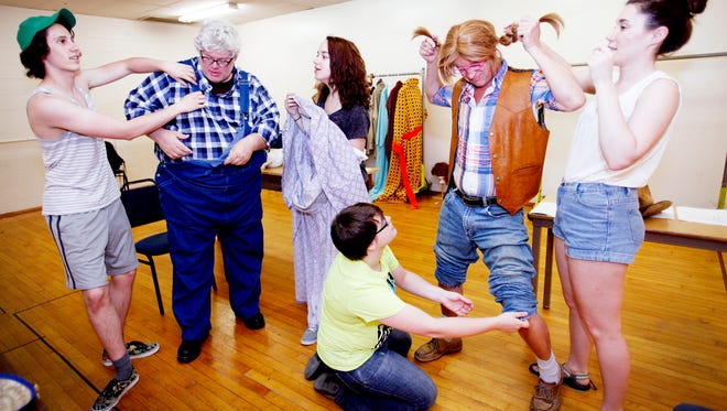 """Dressing crew, from left, Z Hansen, Allison Jordan, Tia Turner and Sami Wyatt help actors Joel P. Rogers, left and Bryan Mercer with one of many costume changes during a rehearsal of the production """"Greater Tuna"""" June 22. """"They are as much a part of what's going on onstage. The dressers are critical,"""" said director Jessica Phelps West of the crew that helps manage costumes for 20 different characters."""