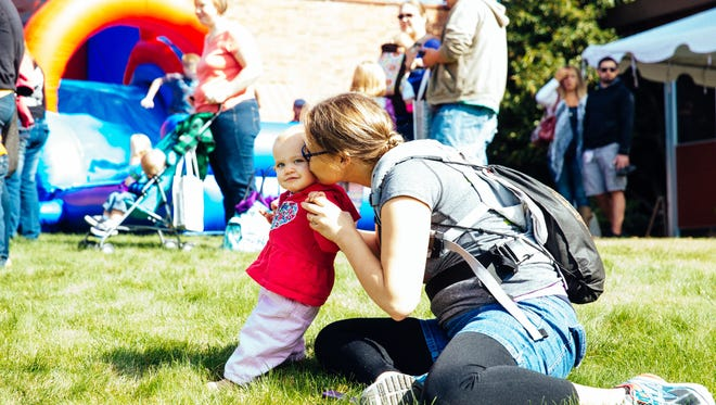 Mom kissing baby in front of the bounce house at Santiam Hospital's Mommy & Baby Palooza hosted in 2016 by the Stayton hospital's Family Birth Center and Santiam Women's Clinic.