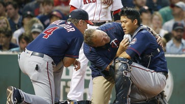Minnesota Twins manager Paul Molitor (4) and a trainer tend to Kurt Suzuki, right, who was injured on a pitch during the second inning Saturday against the Boston Red Sox in Boston. Suzuki left the game and received stitches.