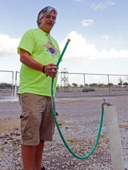 Steve Hanson, vice president of the Las Cruces Youth Soccer League, holds a hose that is the only source of drinking water at one of the High Noon soccer fields.