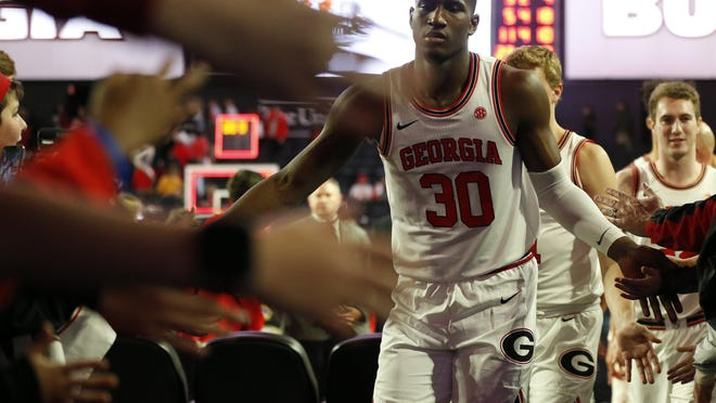 Georgia's Mike Peake (30) slaps hands with fans after winning an NCAA game between Georgia and Georgia Tech in Athens, Ga., on Wednesday, Nov. 20, 2019. Georgia won 82-78.
