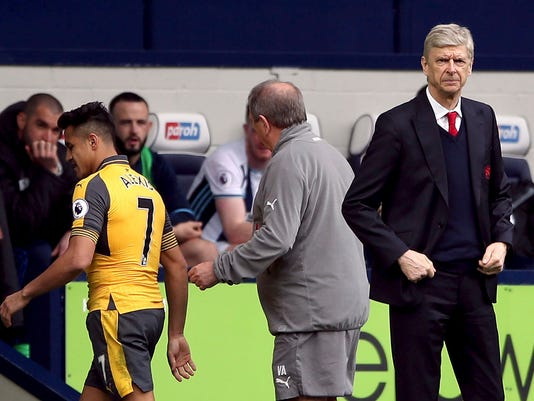 Arsenal manager Arsene Wenger, right, stands on the touchline as Alexis Sanchez , left, is substituted, during the English Premier League soccer match between West Bromwich Albion and Arsenal,  at The Hawthorns, in West Bromwich, England, Saturday March 18, 2017.  (Nick Potts/PA via AP)